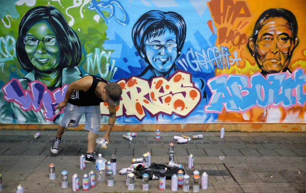 L'artiste graffeur Vestar Fu devant son oeuvre : un graffiti présentant (de gauche à droite) : Tsai Ing-wen du DPP, Hung Shiu-chu du KMT et James Soong du PFP.