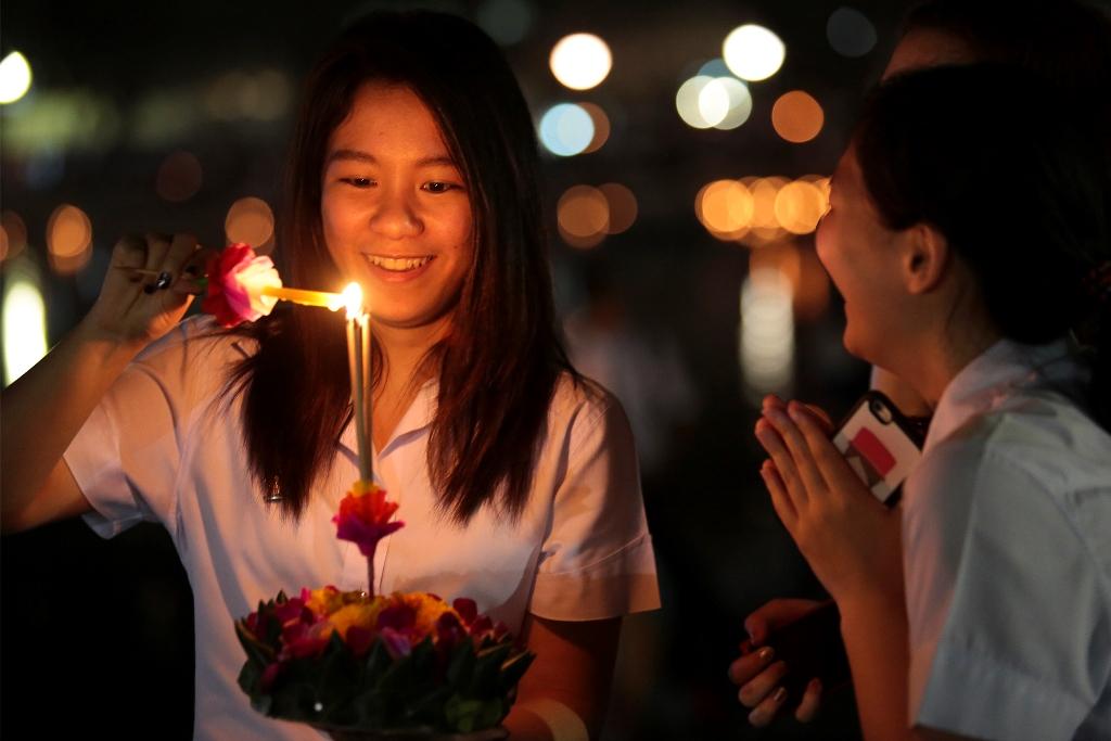 """Une jeune fille thaïlandaise allume de l'encens lors du """"Festival de la pleine lune et des lanternes volantes"""", à Chiangmai le 22 novembre 2015."""