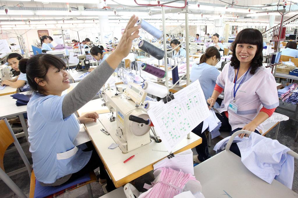 Deux employées s'affairent avec leur machine à coudre, dans une usine textile d'Hanoï.