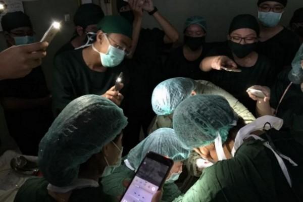 Des chirurgiens birmans opèrent à la lueur de leur smartphone.