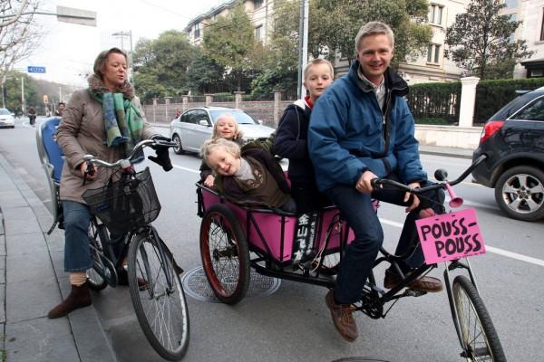 Un français, Loïc Delcroix, responsable financier chez Dongfeng Citröen, et sa famille sur un tricycle chinois typique dans les rues de Shanghaï.