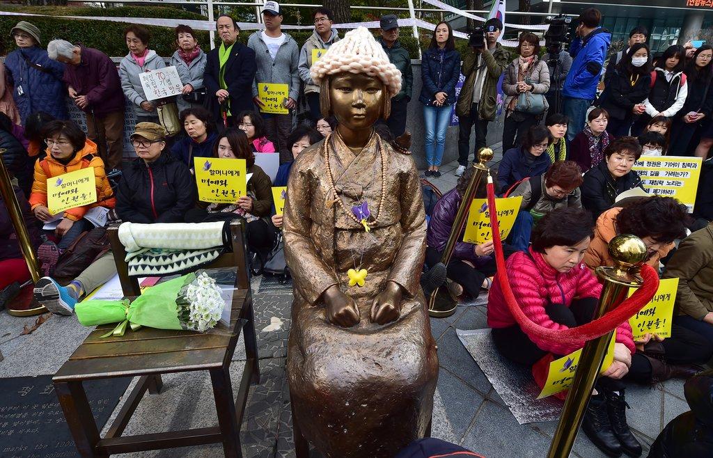 """Le 11 novembre 2015, des manifestants sont assis à côté de la statue symbolisant les """"Femmes de réconfort"""" coréennes."""