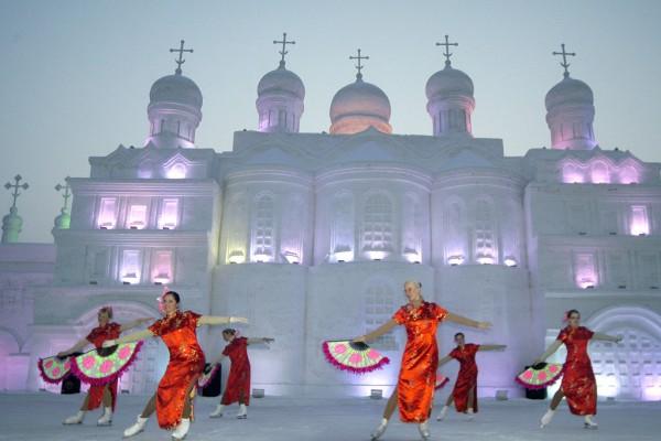 Des danseurs russes exécutent des danses traditionnelles devant l'une des gigantesques sculptures de glace du festival d'Harbin.