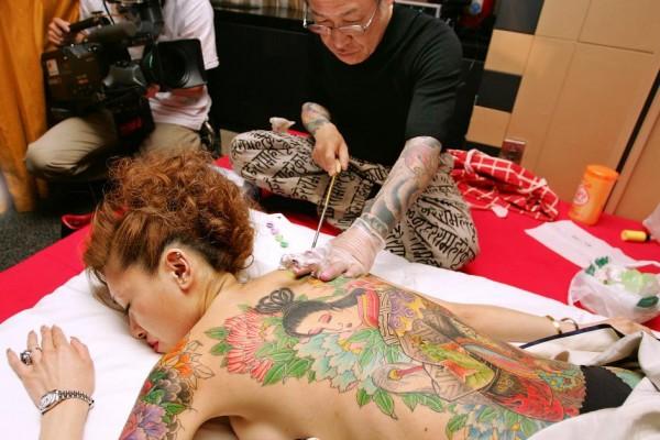 Horiyoshi, l'un des plus grand tatoueurs du Japon, à l'oeuvre durant une performance pour la presse à Tokyo, le 25 mai 2005.