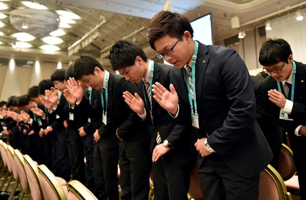 Les nouvelles recrues chez le géant des supermarchés japonais Seven Eleven, ici en pleine cérémonie de formation au langage des signes face à des clients mécontents, à Tokyo, le 19 mars 2015.