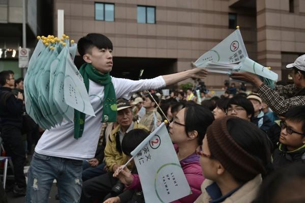 Un jeune militant du parti démocrate-progressiste, vainqueur historique de la présidentielle et des législatives à Taïwan, distribue des drapeaux aux fidèles du parti à la clôture des bureaux de vote le 16 janvier 2016 à Taipei.