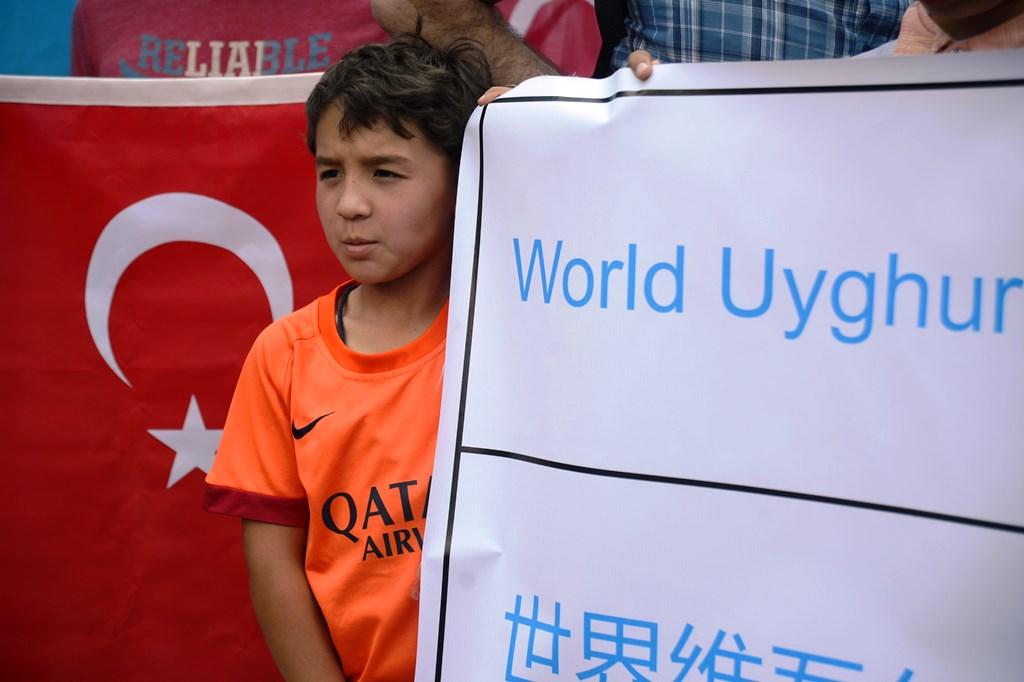 Un enfant ouïghour tient une banderole lors d'un rassemblement devant l'ambassade de Thaïlande à Ankara le 9 juillet 2015, pour protester contre le renvoi de 115 Ouïghours ayant migré à Bangkok vers la Chine contre leur volonté