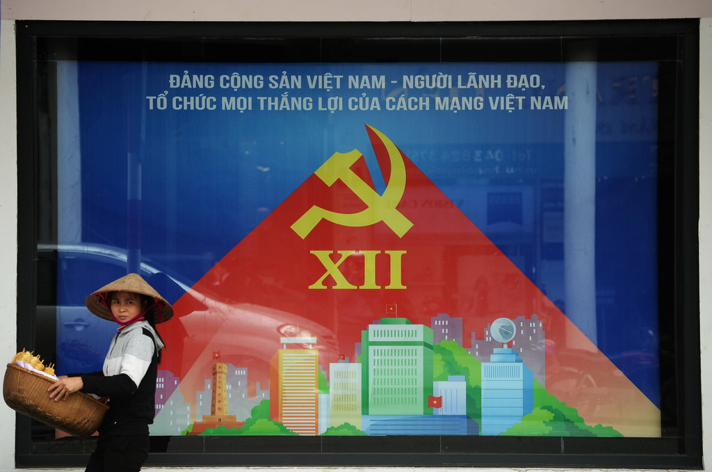 A Hanoi, un vendeur ambulant passe devant une affiche annonçant la réunion prochaine du XIIème Congrès du parti communiste vietnamien
