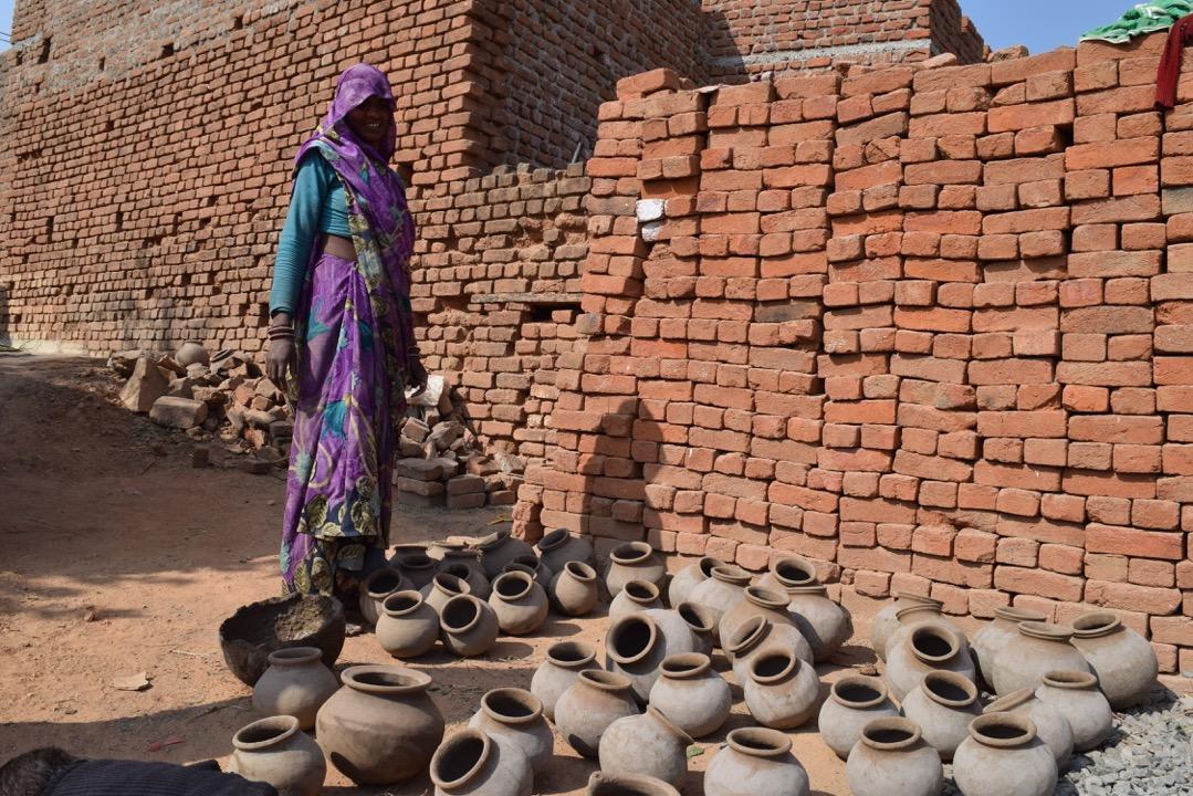 Femme qui fait donc des pots de terre pour survivre.