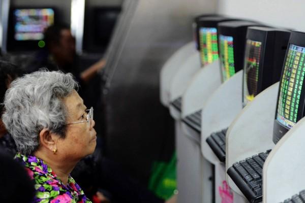 Une personne âgée chinoise surveille ses investissements en bourse à Qingdao dans la province du Shandong.