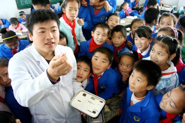 Un professeur présente à ses élèves de primaire des aiguilles d'acupuncture durant une classe de présentation de la médecine chinoise.