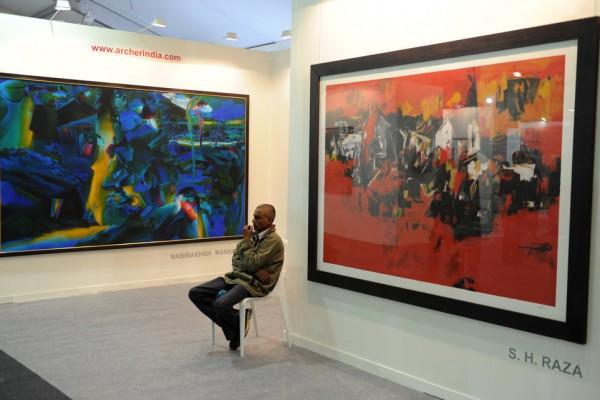 Un agent de sécurité assis surveille des peintures de l'artiste indien S.H. Raza lors de l'India Art Fair de Delhi
