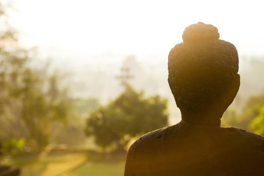 Une statue de Bouddha en pierre dans le soleil du matin.