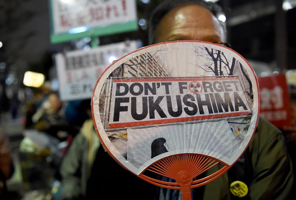 Un manifestant japonais tient un éventail anti-nucléaire lors d'un rassemblement devant le parlement à Tokyo le 11 mars 2016.