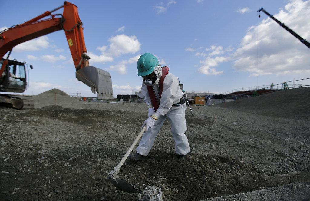 Un ouvrier portant une combinaison protectrice terrasse la terre dans l'enceinte de la centrale gérée par Tokyo Electric Power Co's dans la préfecture de Fukushima