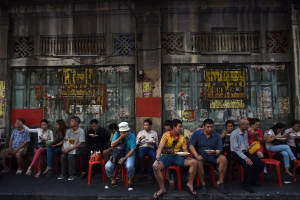 Des jeunes gens déjeunent dans un restaurant de rue de Bangkok le 4 février 2016.