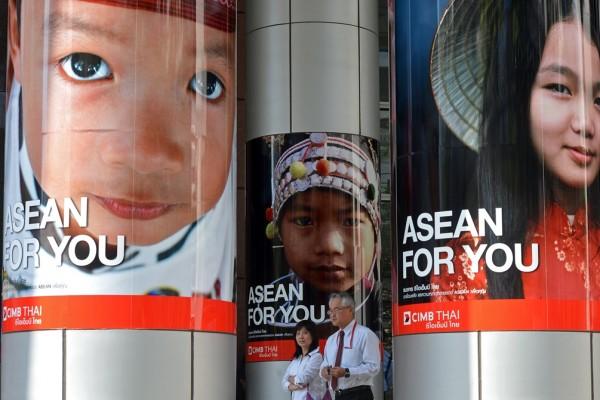 Des employés de bureau thaïlandais passent devant une publicité pour la Communauté économique de l'ASEAN à Bangkok le 14 janvier 2013.