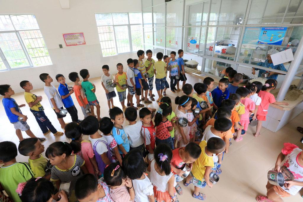 Des enfants d'une école de Liuzhou dans la province chinoise du Guangxi font la queue pour recevoir leur déjeuner.