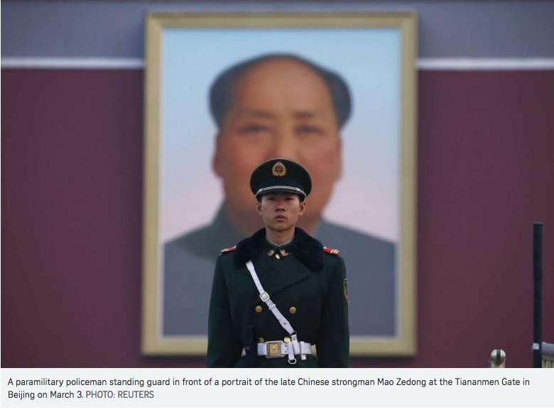 Un soldat chinois se tient debout devant le portrait de Mao Zedong.