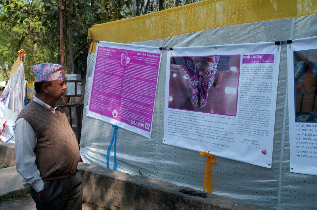 """Le préfet du département de Banke, dans les jardins de la préfecture à Nepalgunj au Népal, devant une pancarte portant le témoignage d'une survivante du trafic d'êtres humains dans le cadre de l'exposition """"Radiant Women""""."""