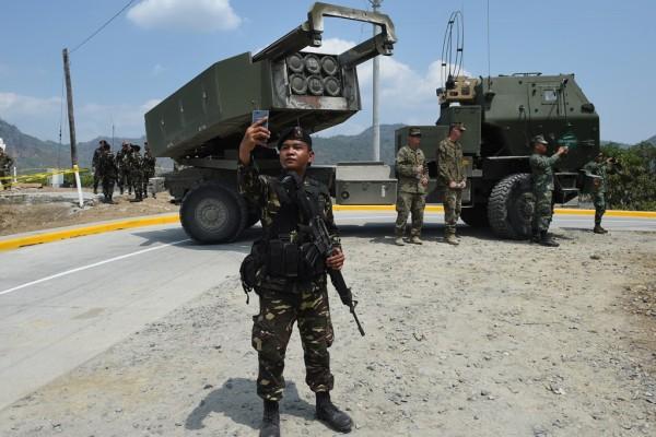 Un soldat philippin prend un selfie devant le système de missile américain M142 High Mobility Artillery Rocket System (HIMARS)