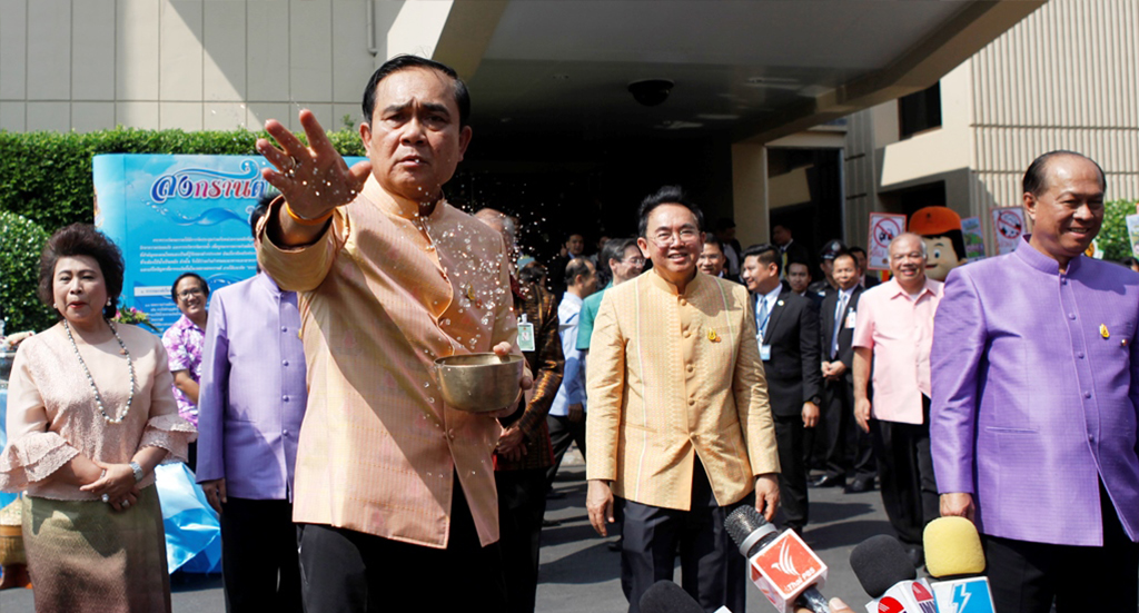Le Premier ministre thaïlandais Prayuth Chan-ocha jette de l'eau sur un groupe de journalistes devant le bâtiment du gouvernement avant le conseil des ministres le 5 avril 2016 à Bangkok.