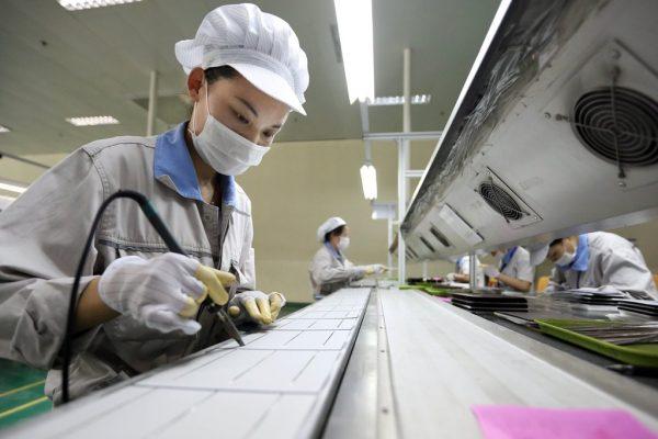 Une ouvrière chinoise travaille sur des cellules photovoltaïques pour panneaux solaires destinés à l'exportation vers l'Europe et les Etats-Unis, à l'usine de Shanghai Shenzhou New Energy Development Co., Ltd, dans la ville de Lianyungang, dans la province chinoise du Jiangsu, le 21 mai 2014.