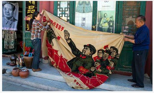"""Des vendeurs dans un marché de curiosités à Pékin déploient une banderole représentant Mao Zedong """"inspectant la grande armée de la Révolution culturelle"""". Copie d'écran du Global Times, le 17 mai 2016."""