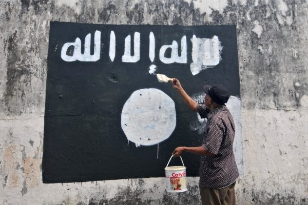 Un employé du gouvernement détruit la peinture d'un drapeau de l'Etat islamique dans la ville de Surakarta (Solo) dans la province de Java Central pour décourager la promotion du groupe djihadiste en Indonésie.