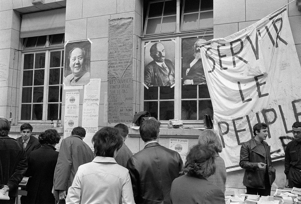 """Les étudiants en grève sont rassemblées dans la cour intérieure de la Sorbonne occupée, à Paris, le 20 mai 1968, pendant les événements de mai-juin 1968. Une banderole avec le slogan """"Servir le peuple"""" est déployée à côté d'affiches de Mao Zedong, Lénine et Karl Marx."""
