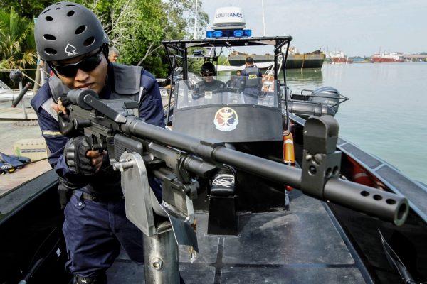 Un membre de la Malaysian Maritime Enforcement agency dans un bateau de défense à coque rigide fabriqué au Canada, après une cérémonie de passage témoin à Malacca, à 148 km de Kuala Lumpur le 18 juin 2014.