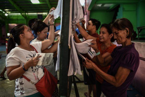 Des électeurs philippins cherchent leur nom sur les listes d'émargement avant d'aller voter aux élections présidentielles, parlementaires et locales, à Manille le 9 mai 2016.