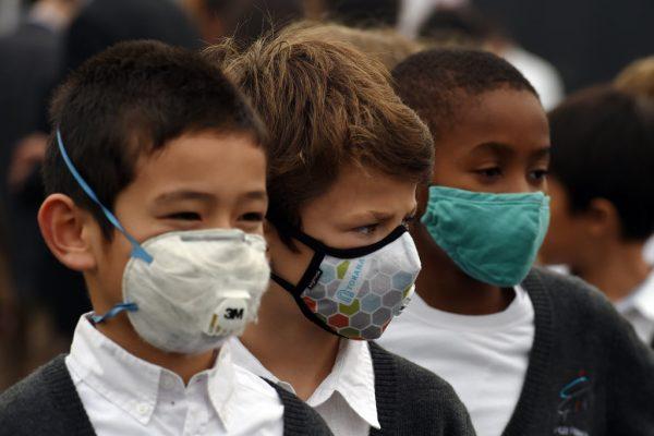 Des enfants portant un masque anti-pollution lors de la cérémonie de lancement des travaux du nouveau lycée français international Charles de Gaulle à Pékin, le 19 octobre 2014.