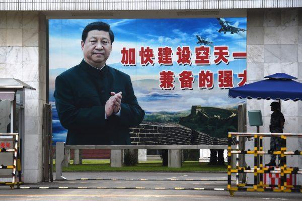 """Sur un panneau géant à Guilin, dans la province chinoise méridionale du Guangxi le 13 mai 2016, le président chinois Xi Jinping applaudit le slogan suivant : """"Accélérer le renforcement d'une armée de l'air puissante et aguerrir les capacités d'attaque et de défense""""."""