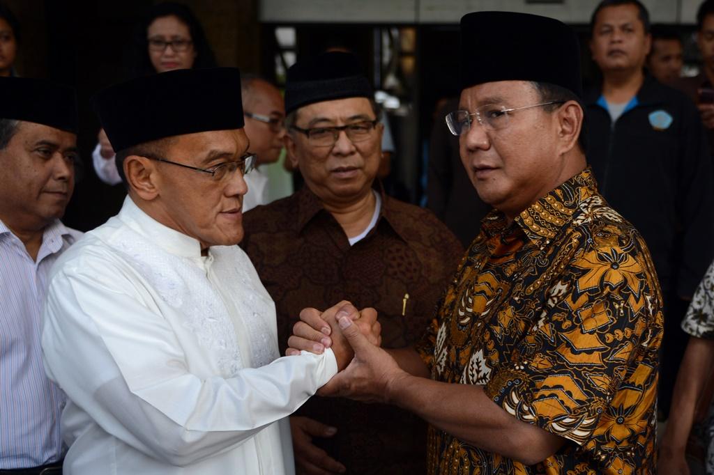 Prabowo Subianto, candidat à la présidentielle indonésienne de 2014 sert la main du magnat des médias Aburizal Bakrie, leader parti Golkar après un meeting avec des organisations islamiques à Jakarta, le 15 juillet 2014.