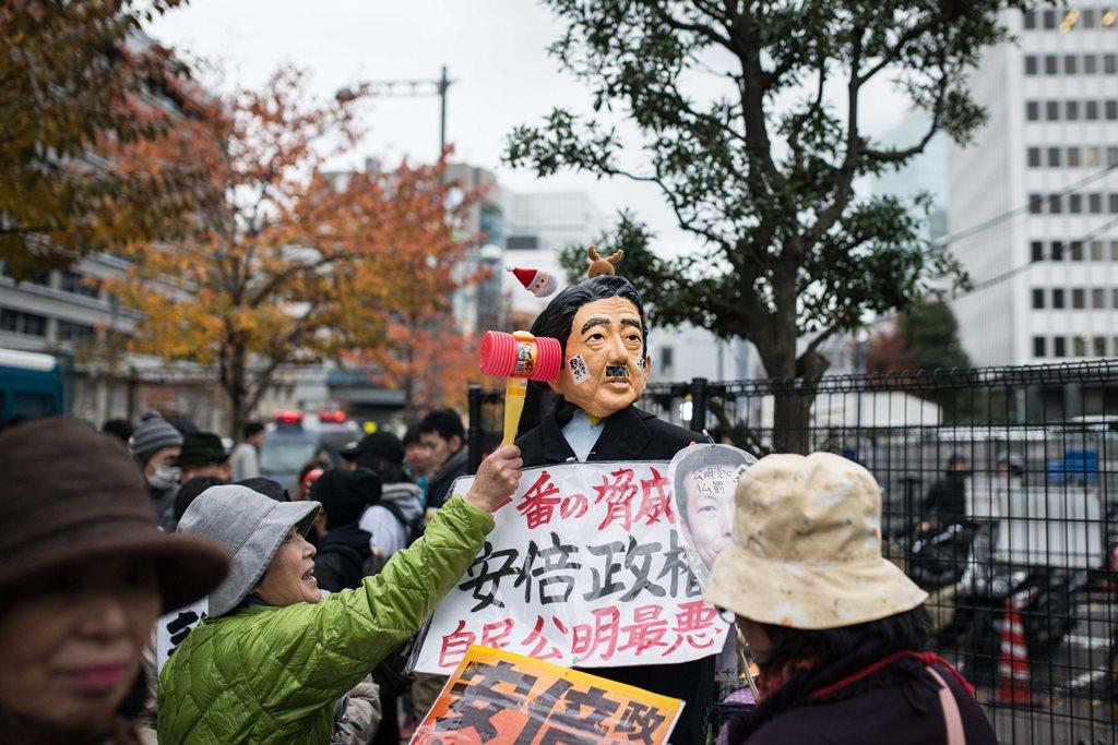 Une femme donnant un coup de marteau à la marionnette représentant le Premier ministre Shinzo Abe, en signe de protestation contre sa politique.