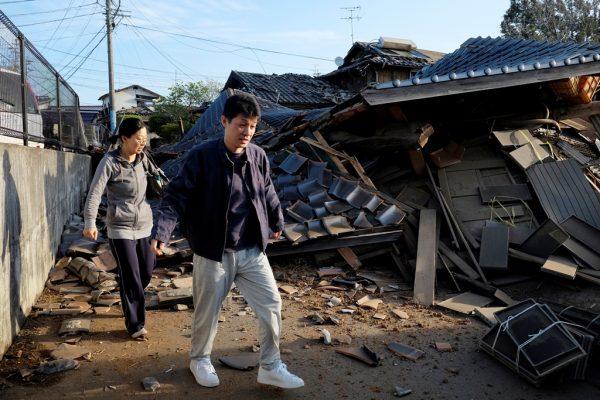 Un couple de Japonais se dirige vers leur ancienne maison écroulée à cause du séisme du 16 avril, à Mashiki, préfecture de Kumamoto dans le sud-ouest du Japon.