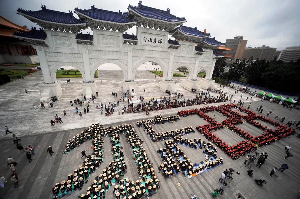 """Des militants pro-indépendance forment les caractères """"N'oublions pas le 28 février"""" (""""Huwang 228"""") sur une place de Taipei le 28 février 2009, en mémoire du massacre perpétré par les forces du Kuomintang."""