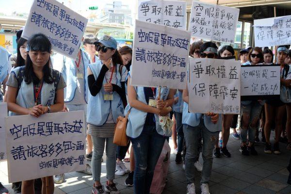 """Des employées de la compagnie China Airlines en grève arborent des pancartes où l'on peut lire """"Se battre pour le droit des travailleurs, c'est aussi garantir de bonnes conditions de sécurité en vol""""."""