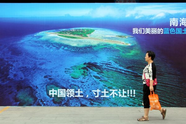 """Un femme chinoise passe devant un poster géant de la mer de Chine du Sud avec le slogan """"Ne cédons jamais un centimètre du territoire de la Chine !"""", dans un rue de Weifang dans la province du Shandong sur la côte nord-est de la Chine, le 14 juillet 2016."""