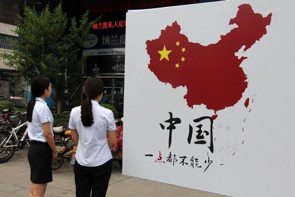 """Des piétons regardent la carte de la Chine avec la """"ligne à neuf traits"""" en mer de Chine du Sud et l'inscription en chinois """"On ne peut rien enlever !"""", dans une rue de Weifang dans la province du Shandong sur la côte nord-est de la Chine, le 14 juillet 2016."""