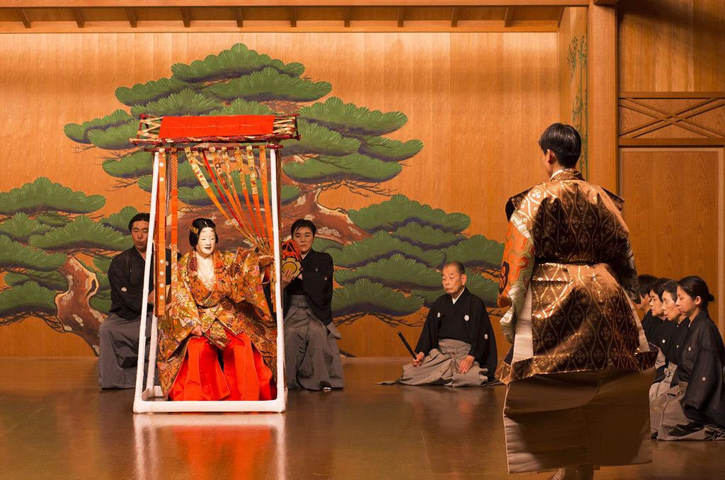 L'envoyé de l'empereur Tang Xuanzong (à droite) rencontre Yang Guifei (à gauche), jouée par le shite (acteur principal), qui porte un masque de femme. Derrière, les musiciens (flute traversière, petit et grand tambours japonais en forme de diabolo) ; à droite, les chanteurs.