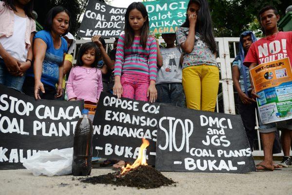 Des résidents de Calaca regardent brûler un tas de terre ramassé à côté de la centrale à charbon dans leur ville, lors d'une manifestation devant le bureau du ministère de l'Environnement à Manille aux Philippines le 17 mars 2016.