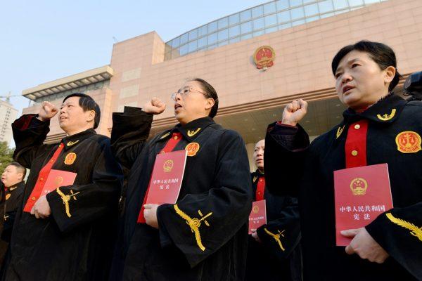 """Des juges chinois de la court intermédiaire du peuple de Bengbu, dans la province de l'Anhui près de Shanghai, prêtent serment pour marquer la première """"Journée de la Constitution en Chine"""", le 4 décembre 2014."""