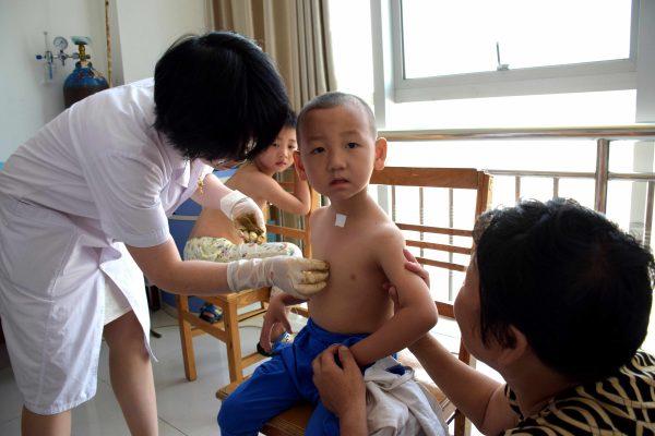 Un jeune garçon chinois en pleine consultation à l'hôpital du peuple de la ville de Zhumadian, dans la province du Henan au centre de la Chine, le 13 juillet, 2015.