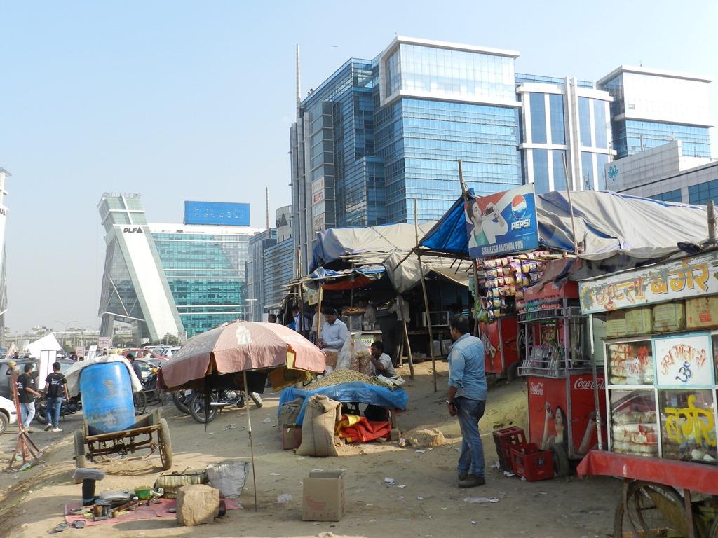 Visage de Delhi aujourd'hui : buildings ultra-modernes juxtaposés à la misère des vendeurs de rue.