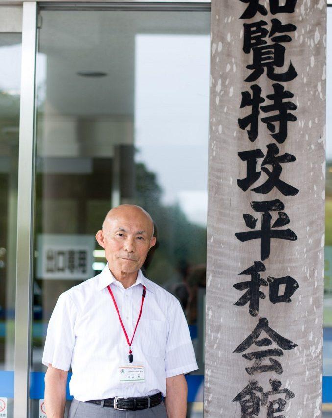 Takeshi Kawatoko devant l'entrée du Musée pour la paix de Chiran. Né en août 1940, il a grandi à Chiran jusqu'à son entrée à l'Académie de Défense. Colonel retraité des forces terrestres d'autodéfense, il est aujourd'hui conseiller au Musée pour la paix de Chiran.