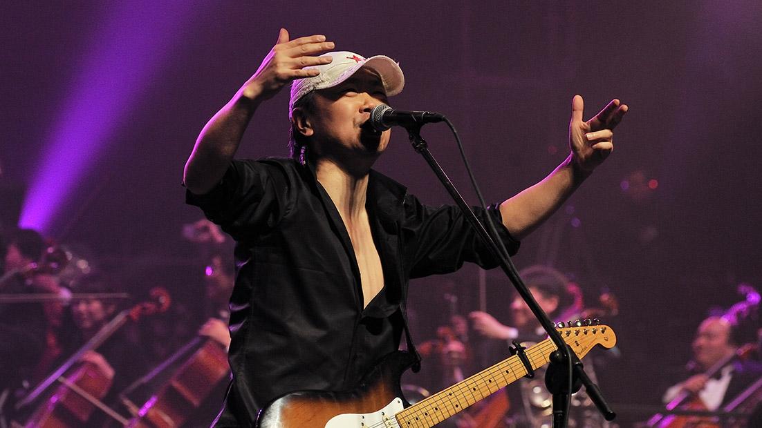 """Le guitariste-chanteur Cui Jian, surnommé le """"parrain du rock chinois"""", avec le chef d'orchestre Tan Lihua et l'orchestre philarmonique de Pékin lors du """"Rock Symphony New Year's concert"""" le 31 décembre 2010 au Gymnase des Travailleurs de Pékin."""