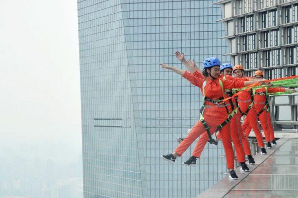 Des visiteurs équipés de harnais et de protections à l'extérieur du 88ème étage de la Tour Jinmao dans le quartier de la finance de Lujiazui, dans le district de Pudong à Shanghai, le 28 juillet 2016.