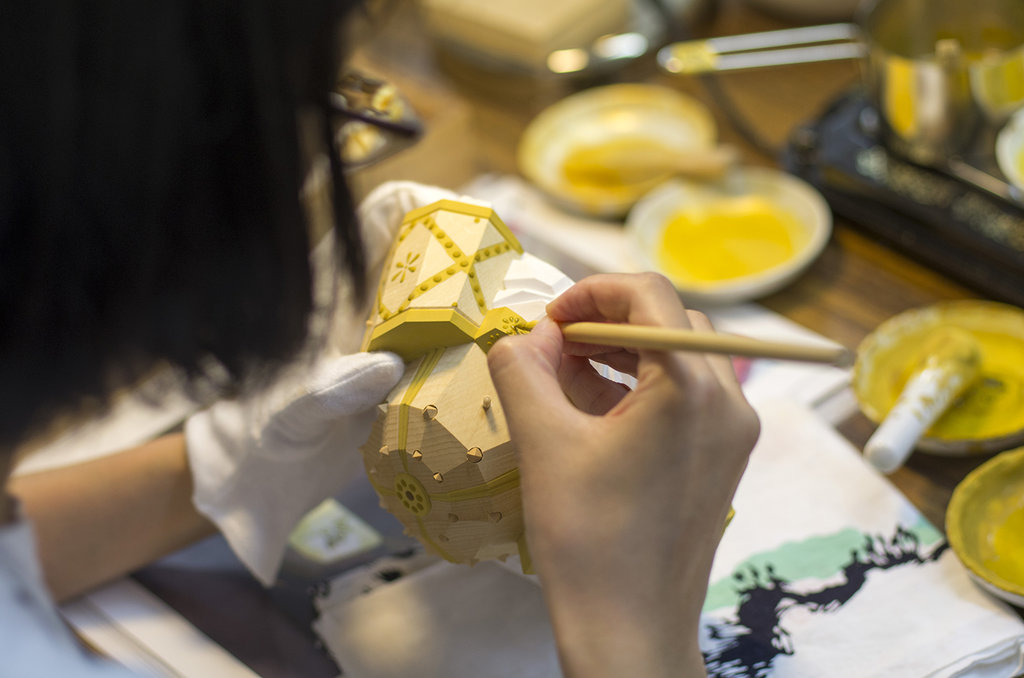 Yôko Matsumoto, épouse d'Ippei, applique avec précision de la peinture sur une pièce représentant un casque de samouraï.